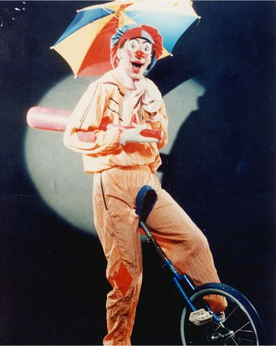 clown juggles on unicycle
